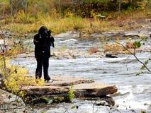 Женщина коренного американца фотографируя речные пороги в древесинах стоковое изображение rf