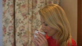 женщина кофе выпивая домашняя Портрет счастливой блондинкы с кружкой в руках видеоматериал