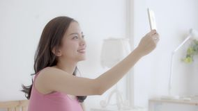 Женщина красивого портрета молодая азиатская сидя принимающ selfie с умным мобильным телефоном на спальне в утре дома сток-видео