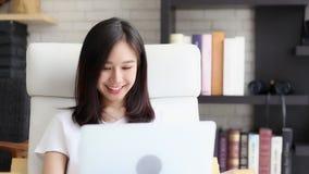 Женщина красивого портрета независимая азиатская работая онлайн ноутбук с улыбкой и счастливым усаживанием на кресле на живя комн