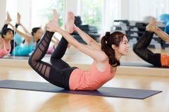 Женщина красивого sporty yogi пригонки азиатская практикует dhanu asana йоги Стоковые Фото