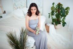 Женщина красивой девушки армянская в голубом платье вечера сидя на кровати в красивом интерьере спальни Стоковые Изображения