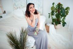 Женщина красивой девушки армянская в голубом платье вечера сидя на кровати в красивом интерьере спальни Стоковая Фотография