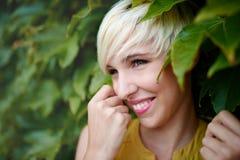 Женщина красивой короткой с волосами платины белокурая стоя против фона загородки плюща Стоковое Фото