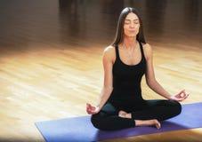 Женщина красивых детенышей подходящая сидя в представлении лотоса на циновке йоги Стоковая Фотография RF