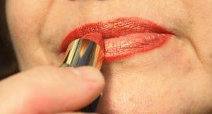 Женщина красит ее губы Стоковые Изображения RF
