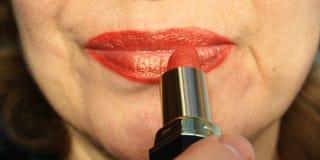 Женщина красит ее губы Стоковое Фото