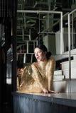Женщина красотки в платье золота представляя на таблице адвокатского сословия Стоковые Изображения