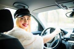 Женщина красоты в автомобиле крытом держит колесо повернуть вокруг смотреть пассажиров в заднем сиденье Стоковая Фотография RF
