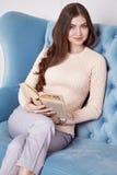 Женщина красоты в стиле свитера шерстей моды совершенной домашней внутренней носки девушки свечи цветка мебели комфорта вскользь  Стоковое Фото