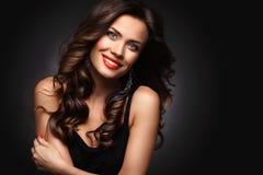 Женщина красоты модельная с длинными волосами Брайна волнистыми Здоровые волосы и красивый профессиональный состав Красные губы и