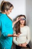 Женщина красоты молодая взрослая проверяет зрение в острословии офтальмолога Стоковое Фото