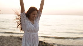 Женщина красоты счастливая усмехаясь на море на замедленном движении захода солнца видеоматериал