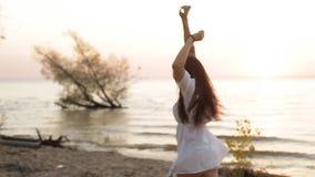 Женщина красоты счастливая усмехаясь на море на замедленном движении захода солнца сток-видео