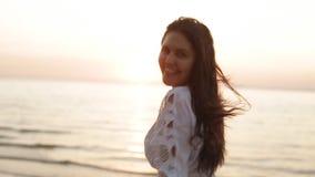 Женщина красоты счастливая усмехаясь на море на замедленном движении захода солнца акции видеоматериалы