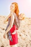 Женщина красоты с младенцем в слинге мама младенца Мать и ch Стоковая Фотография