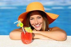 Женщина красоты с совершенной улыбкой наслаждаясь в бассейне на каникулах