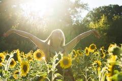 Женщина красоты sunlit на желтых свободе поля солнцецвета и концепции счастья Стоковые Фотографии RF