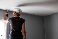Женщина крася края потолка стоковые изображения
