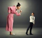 Женщина крича на малом вспугнутом человеке Стоковые Изображения RF