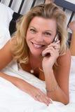 Женщина кровати телефона стоковое изображение