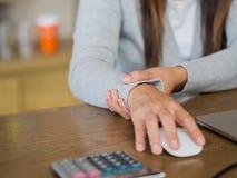 Женщина крупного плана держа ее боль запястья руки от использования компьютера стоковые фото