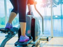женщина крупного плана используя оборудования фитнеса в тренажерном зале Стоковые Изображения RF
