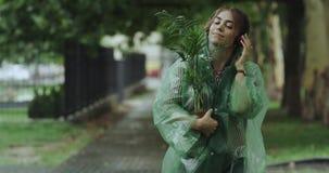 Женщина крупного плана милая с цветком идя вниз с улицы на дне дождя и слушая музыке от наушников видеоматериал
