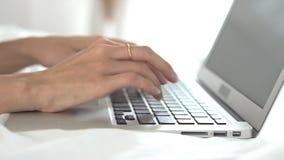 Женщина крупного плана молодая азиатская используя ноутбук для отдыха на спальне, работы девушки онлайн с печатая клавиатурой для
