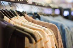 Женщина крупного плана одевает на вешалке в магазине одежды стоковая фотография rf
