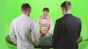 Женщина крупье вручая вне карточки и обломоки для 2 игроков в покере зеленый экран движение медленное акции видеоматериалы