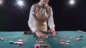 Женщина крупье казино шаркает карточки покера и фокус выполнять с карточками Черная предпосылка яркий свет медленно сток-видео