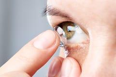 Женщина кладет контактные линзы Стоковая Фотография