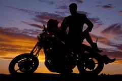 Женщина кладет назад на силуэт стойки человека мотоцикла Стоковые Изображения