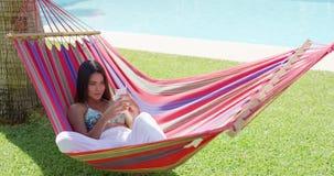 Женщина кладя вниз в гамак пока использующ телефон акции видеоматериалы