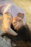 Женщина кладя вниз на пляж песка на заходе солнца Стоковое Изображение