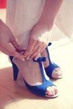 Женщина кладя голубые ботинки дальше Стоковые Изображения RF