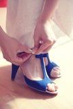 Женщина кладя голубые ботинки дальше Стоковое Изображение