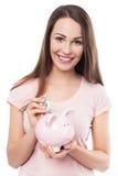 Женщина кладя деньги в копилку стоковое фото rf