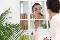 Женщина кладя на губную помаду Стоковая Фотография RF