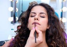 Женщина кладя лоск губы стоковые изображения