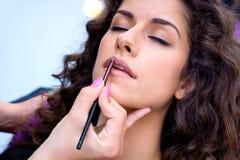 Женщина кладя лоск губы стоковые изображения rf