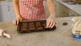 Женщина кладя печенья на лист выпечки сток-видео
