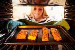 Женщина кладя Salmon филе в печь к кашевару Стоковое фото RF