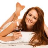 Женщина лежа в кровати с бокалом вина Стоковые Фотографии RF