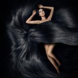 Женщина лежа на волосах и покрывает ее тело стоковая фотография rf