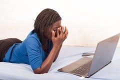 Женщина лежа на кровати и уставшая работать в Интернете стоковое фото