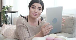 Женщина лежа на софе используя цифровой планшет для видео- звонка видеоматериал