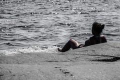 Женщина лежа на утесе в океане смотря вне на горизонте стоковое фото rf