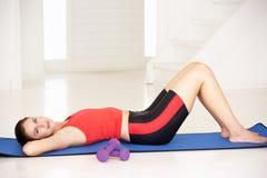 Женщина лежа на циновке тренировки Стоковые Фотографии RF